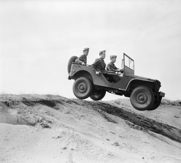 Military Personnel Driving Jeep down Dunes